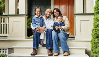 Happy family sits on the porch of their new home