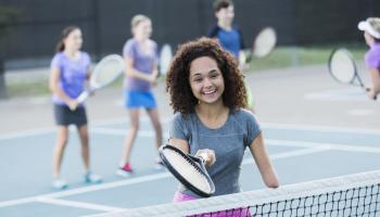 Teenager plays tennis with other young women