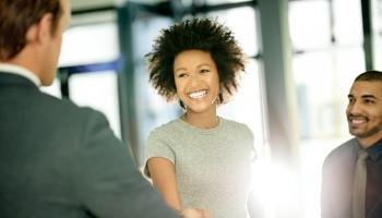 Woman shakes hands with a man in a corporate setting